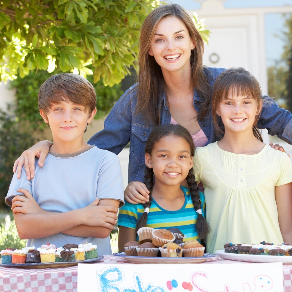 Group of children holding bake sale with mother smiling to camera.