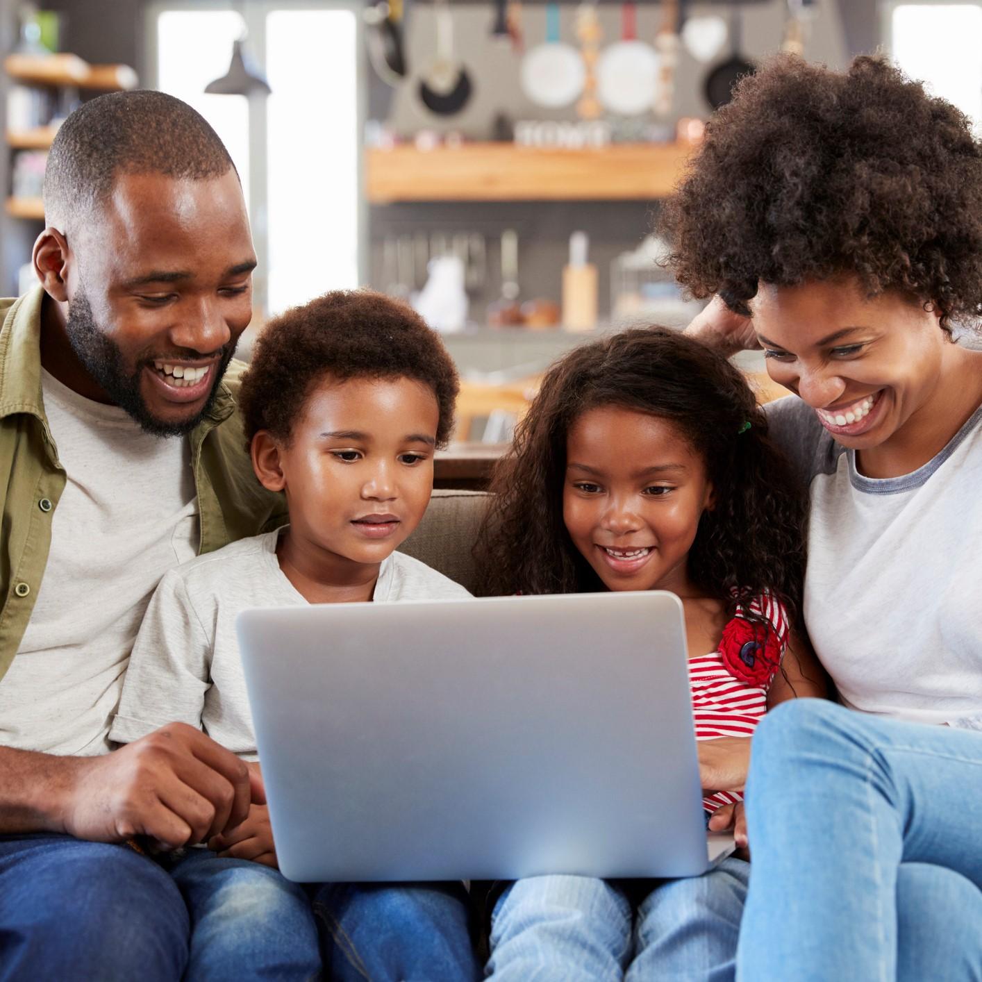 Family sitting on sofa in open plan lounge using laptop